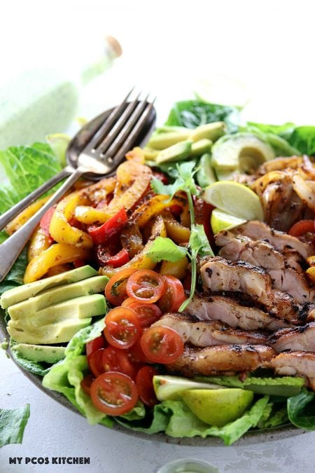 Keto Low Carb Chicken Fajita Salad - My PCOS Kitchen - Grilled fajita chicken over a bed of lettuce, taco peppers and onions.