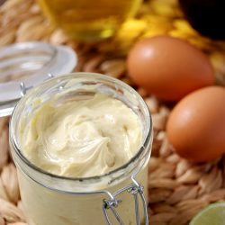 A glass jar full of homemade keto mayonnaise made in an immersion blender.