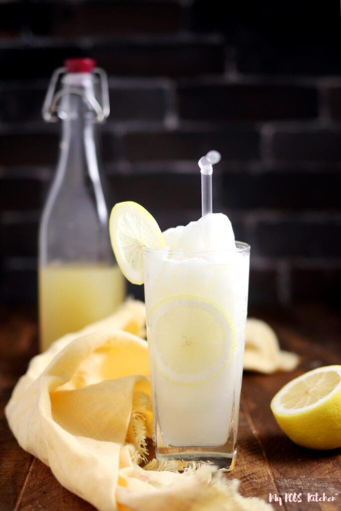 Sugar free frozen lemonade in a glass with some lemon slices and a straw.