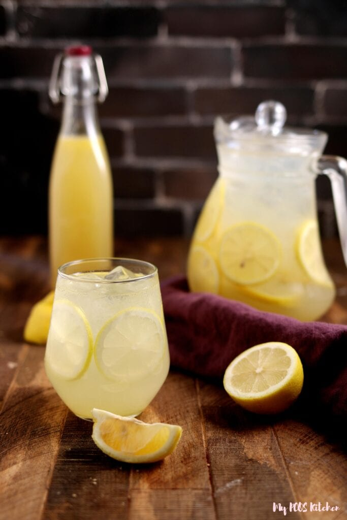A pitcher of freshly squeezed lemonade beside some lemonade syrup and a glass.