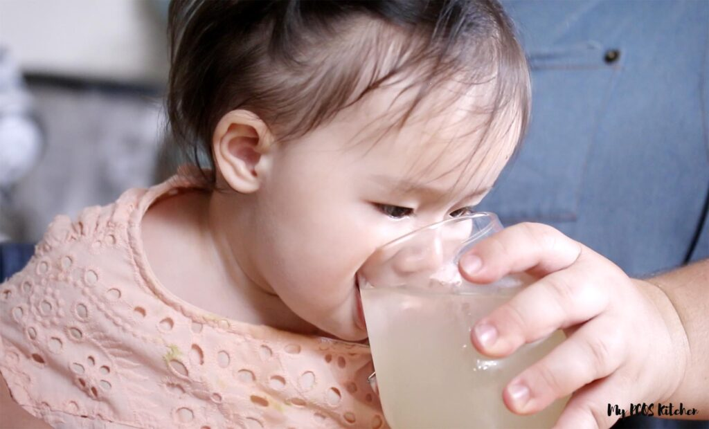 Toddler drinking sugar free lemonade from a glass.