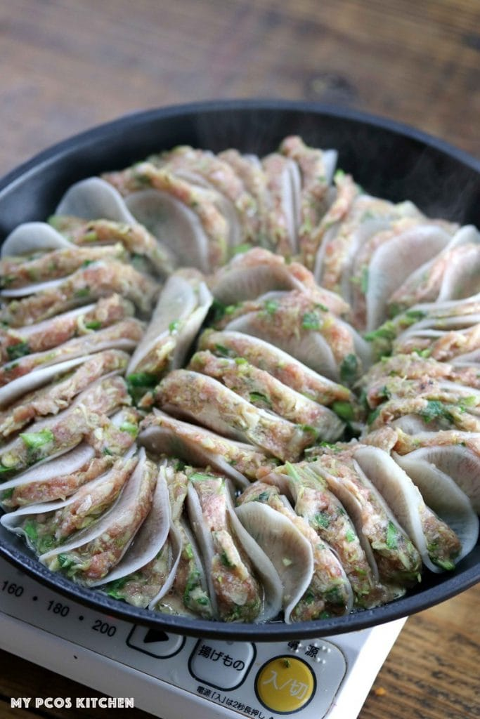 Daikon potstickers lined in a frying pan ready to get fried.
