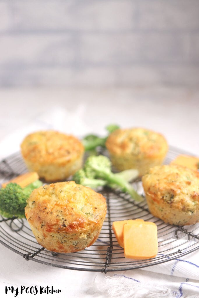 4 jumbo cheese muffins with broccoli on a cooling rack.
