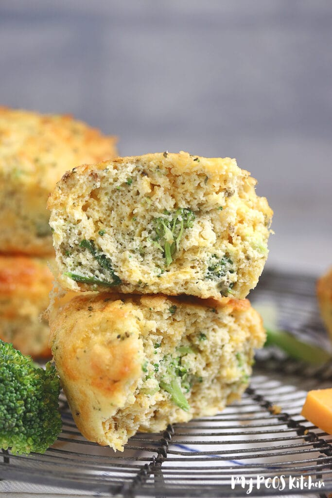 Two savory muffins on top of one another and cut in half to show the broccoli and cheese inside.