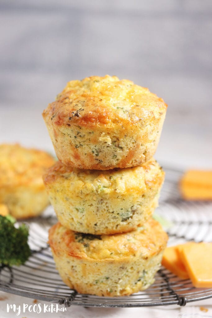 Three cheddar muffins with broccoli stacked on top of each other.
