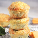 Cheddar broccoli muffins stacked on top of one another for a picture.