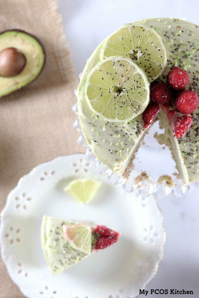 My PCOS Kitchen - Avocado Cheesecake with Lime - An overhead shot of a no bake avocado cheesecake.  Lime slices, raspberries and chia seeds over the cheesecake.