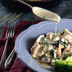 Keto Spinach & Feta Stuffed Chicken Breast with Creamy Sauce - My PCOS Kitchen - A spoonful of starch-free cream gravy is poured over stuffed chicken breasts on a plate.