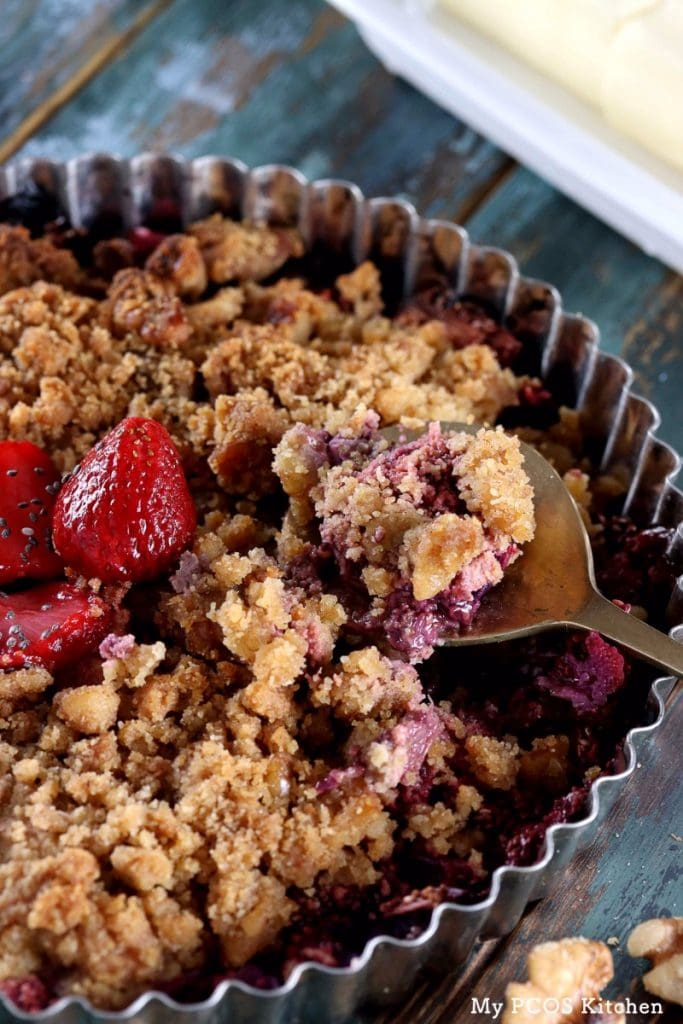 My PCOS Kitchen - Low Carb Strawberry Rhubarb Crisp - A brass spoon filled with a gluten-free and sugar-free crisp. Sweetened with stevia and the crumble is made of nuts.