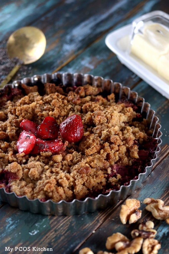 My PCOS Kitchen - Low Carb Strawberry Rhubarb Crisp - A delicious crispy crisp made with sugar-free strawberries and rhubarb.  On a wooden blue surface and brass spoon in the back.