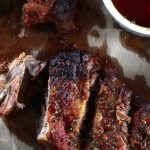 My PCOS Kitchen - Low Carb Smoky BBQ Ribs - Photography shot of ribs from above. Oil stains on parchment paper with homemade sugar-free bbq sauce.
