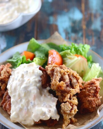 My PCOS Kitchen - Keto Paleo Fried Chicken - Gluten-free, Dairy-free, Grain-free, Pork-Free, Nut-free Fried Chicken - Delicious fried chicken over a blue ceramic plate and covered with dairy-free tartar sauce.