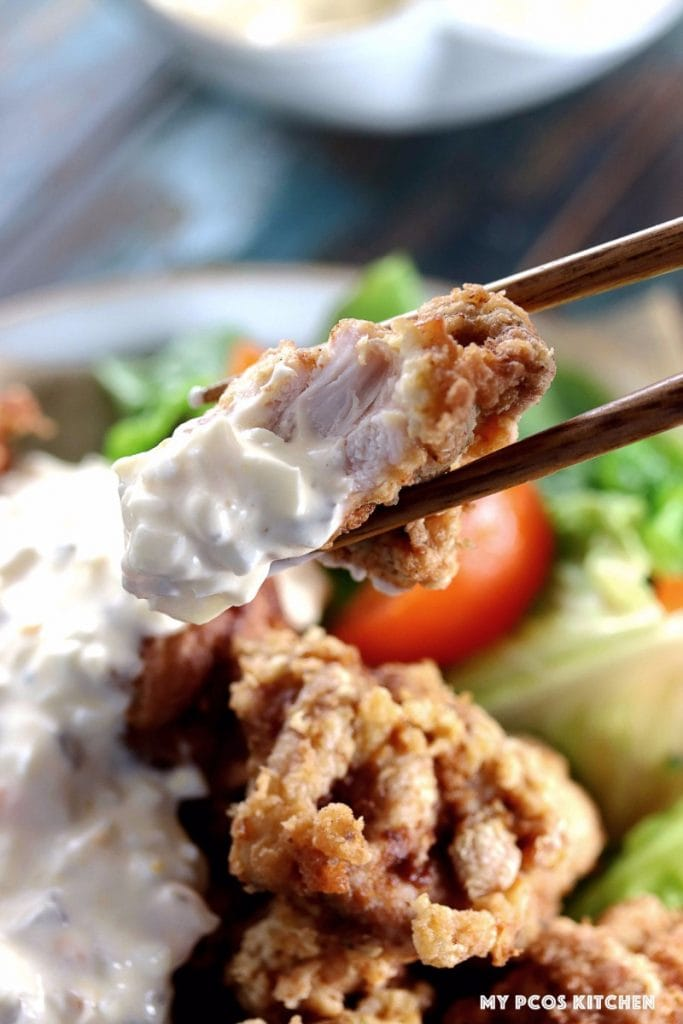 My PCOS Kitchen - Keto Paleo Fried Chicken - Gluten-free, Dairy-free, Grain-free, Pork-Free, Nut-free Fried Chicken - Japanese karaage fried chicken coated in tartar sauce and chopsticks holding a half eaten piece.
