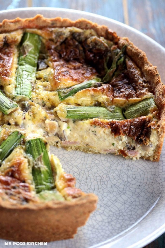 My PCOS Kitchen - Low Carb Quiche with Mascarpone & Asparagus - Asparagus over a tall quiche filled with mascarpone, ham, mushrooms and cheddar. A slice is missing from the quiche.