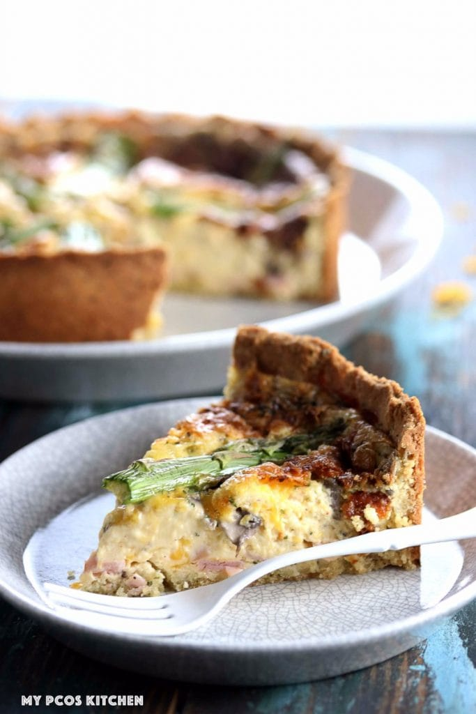 My PCOS KitcheMy PCOS Kitchen - Low Carb Quiche with Mascarpone & Asparagus - A slice of gluten-free quiche over a quite marbled ceramic plate and a white fork. Whole quiche in the background.