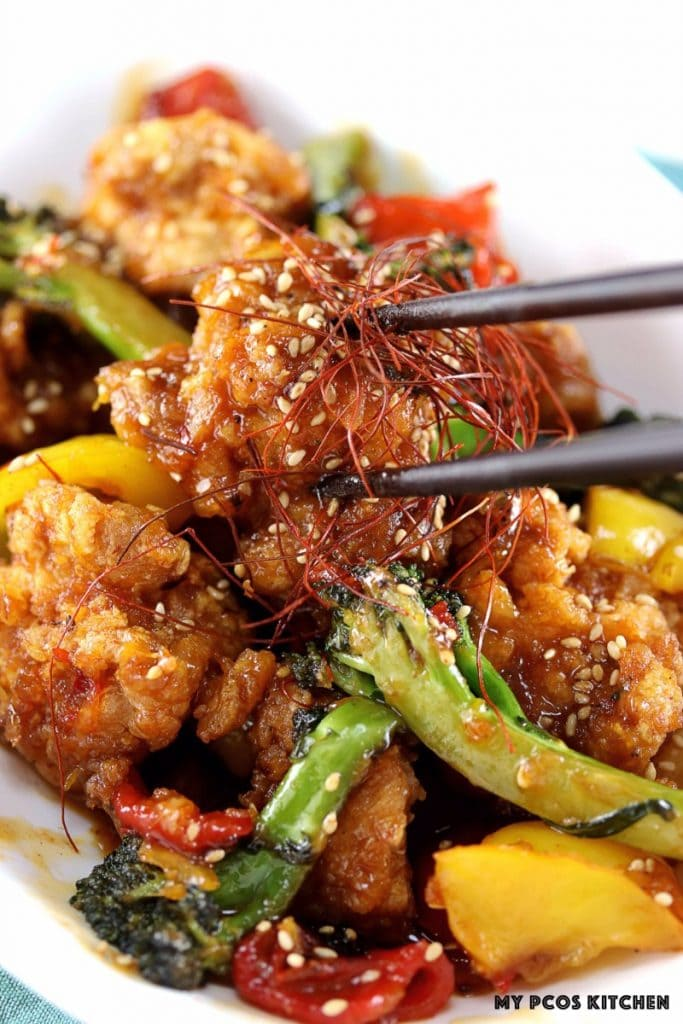 My PCOS Kitchen - Low Carb Sweet Chili Chicken - Some chopsticks holding a piece of fried chicken covered in sweet chili sauce. Keto Fried Chicken pieces in sweet Thai sauce.