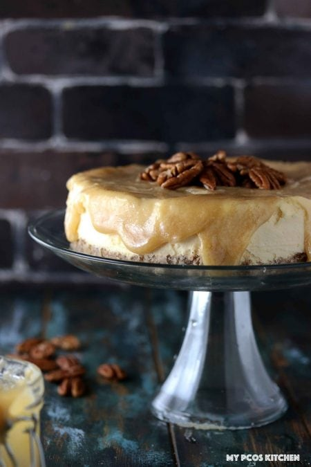Sugar Free Low Carb Caramel Cheesecake - My PCOS Kitchen - An upfront shot of a cheesecake with caramel sauce drizzling from the sides.