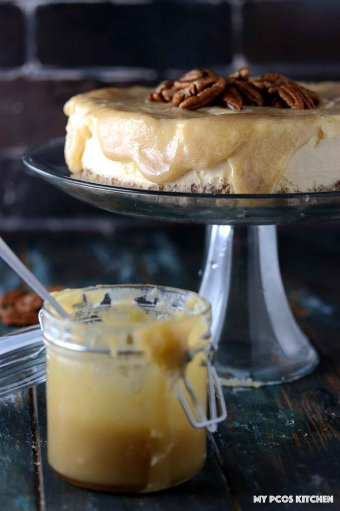 Sugar Free Cheesecake with Caramel - My PCOS Kitchen - Glass of caramel sauce in front of glass cake stand with a gluten-free low carb caramel cheesecake over it.