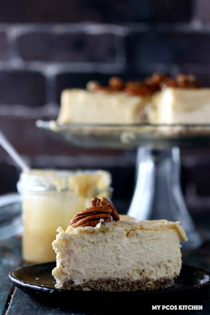 Sugar Free Cheesecake with Caramel - My PCOS Kitchen - A slice of sugar-free cheesecake with caramel sauce over. A whole cheesecake on a glass cake stand and caramel sauce in a glass jar in the background.