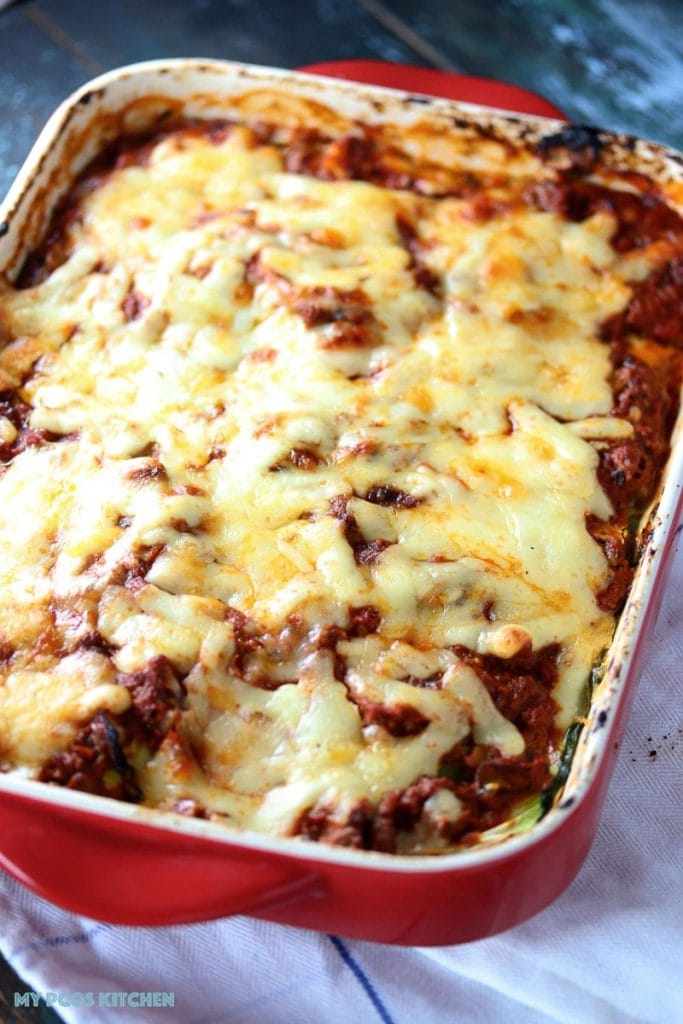 Low Carb Lasagna with Zucchini Noodles - My PCOS Kitchen - A lasagna in bake ware. Cheese is melted and toasted and we can see zucchini lasagna noodles on the side.