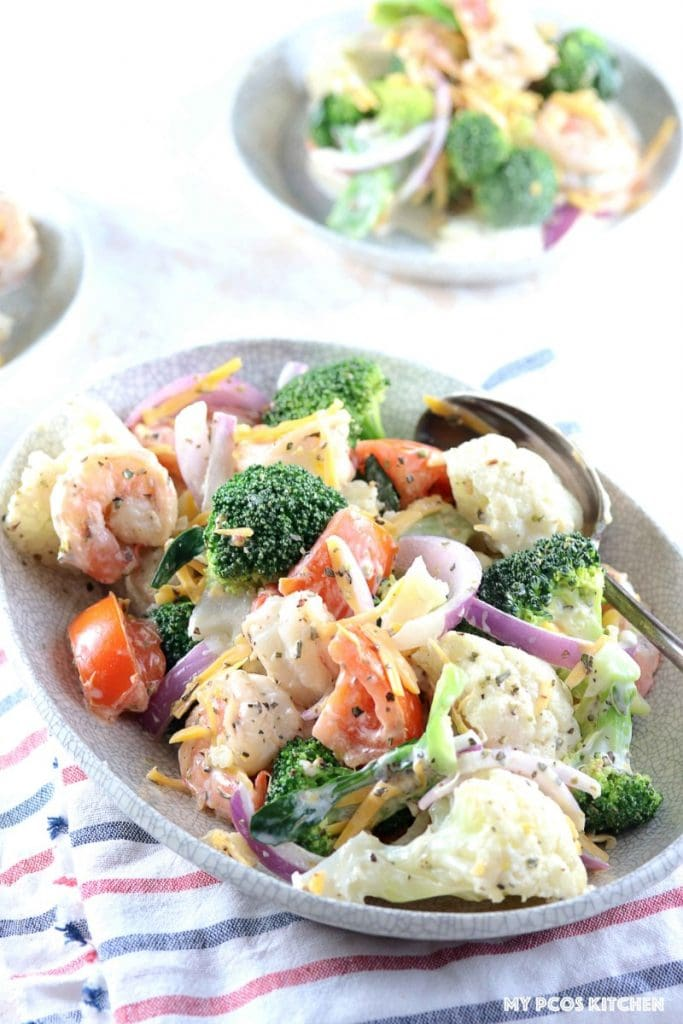 Amish Broccoli and Cauliflower Salad with Shrimps - My PCOS Kitchen - A delicious creamy salad made with healthy vegetables and shrimp. Two small bowls of salad in the background.