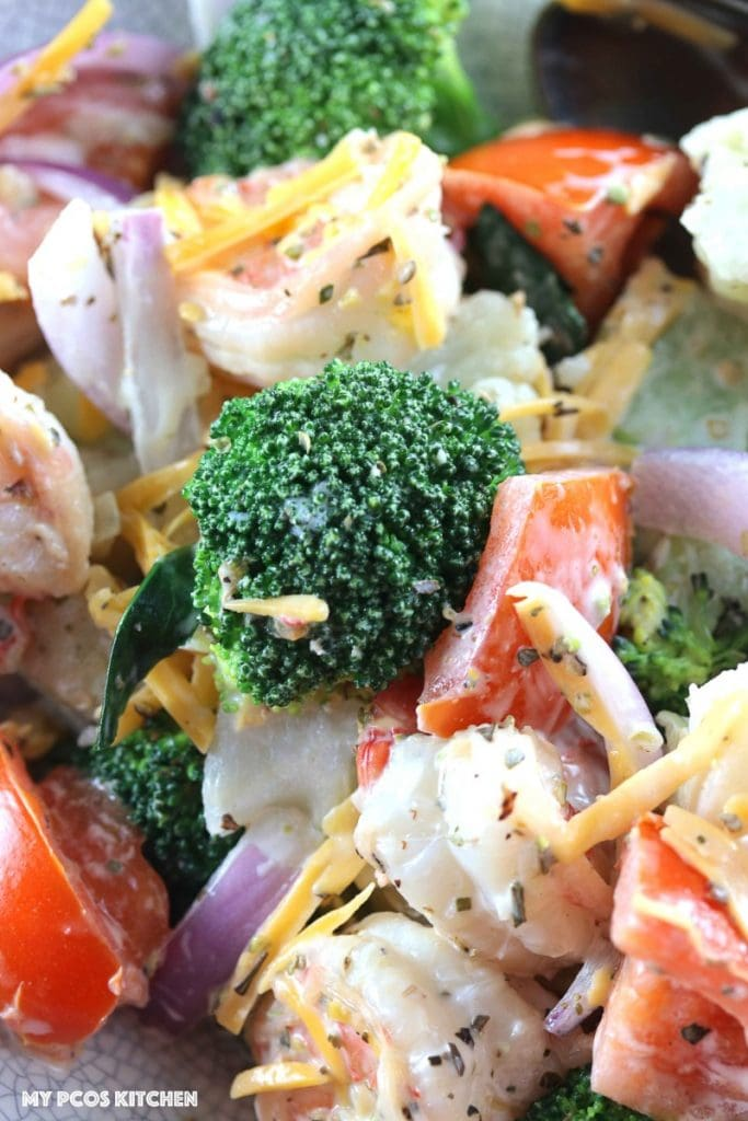 Amish Broccoli and Cauliflower Salad with Shrimps - My PCOS Kitchen - A closeup shot of broccoli and cauliflower salad with tomatoes, red onions and cheddar.