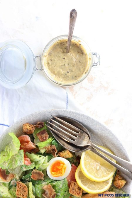 My PCOS Kitchen - Low Carb Homemade Caesar Salad Dressing - gluten-free caesar dressing above a caesar salad.