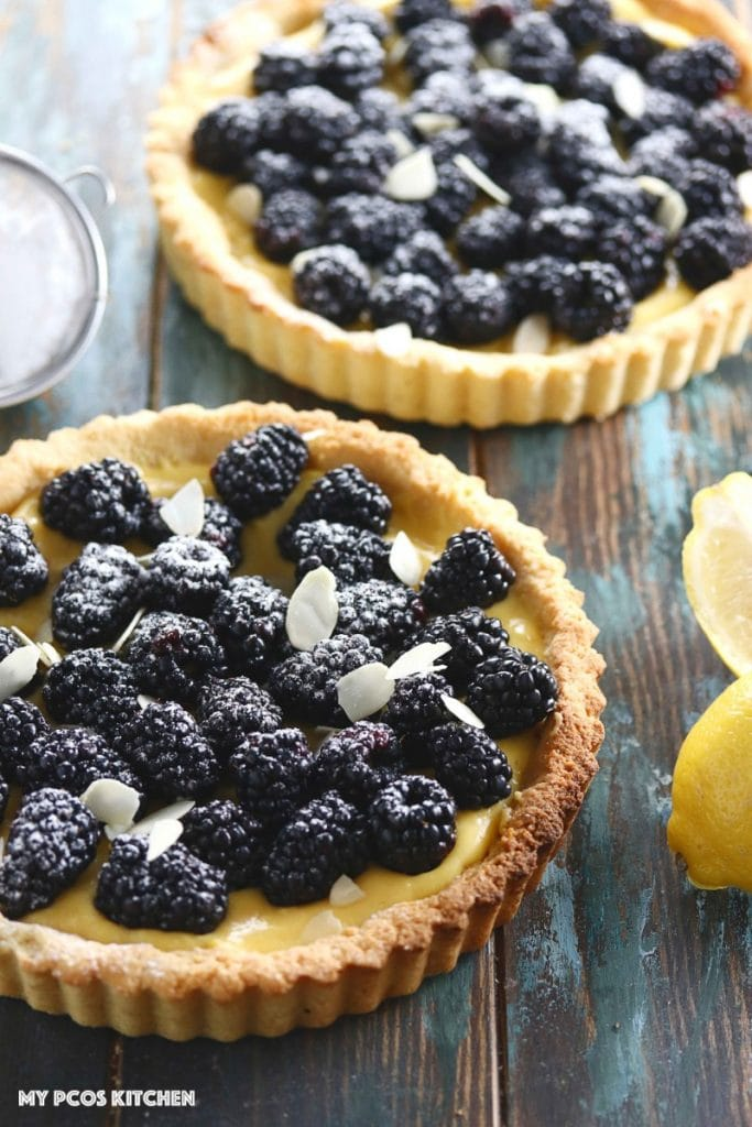 Low Carb Lemon Curd Tart with Blackberries - My PCOS Kitchen - A lemon tart with fresh blackberries and almond slices on top.