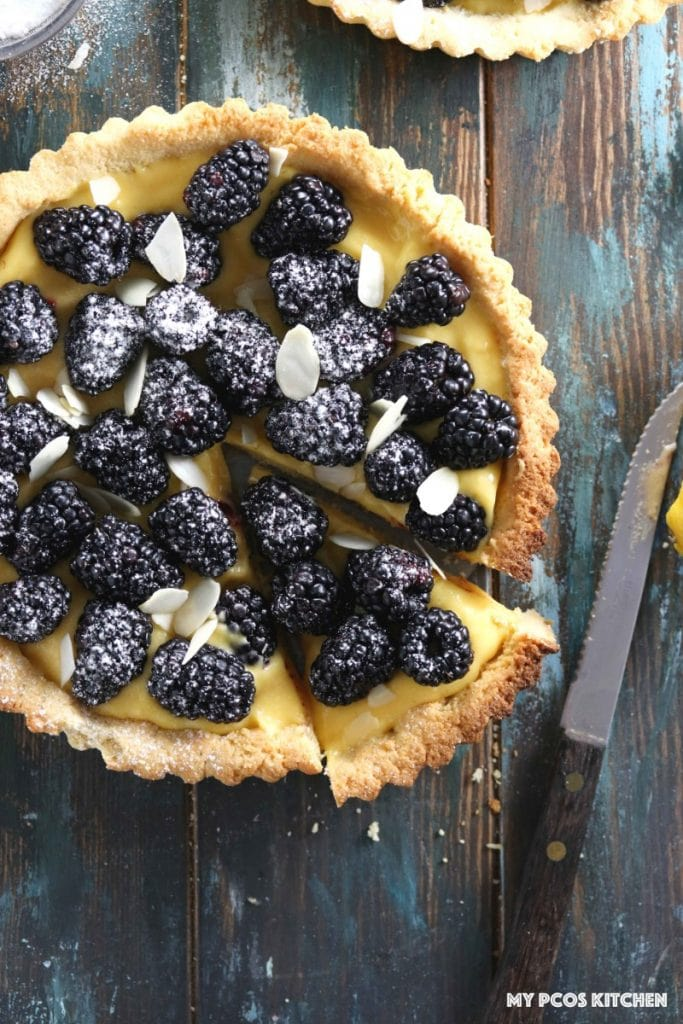 Low Carb Lemon Curd Tart with Blackberries - My PCOS Kitchen - An overhead shot of the whole tart with a rustic knife beside.