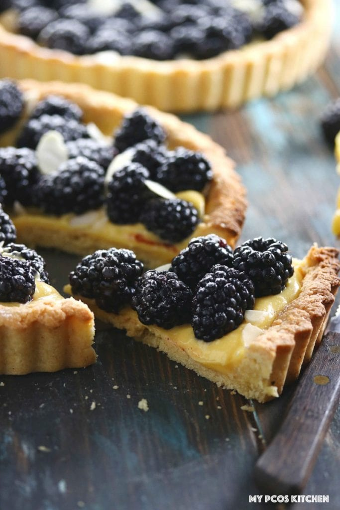 Low Carb Lemon Curd Tart with Blackberries - My PCOS Kitchen - A slice of the tart is taken out.