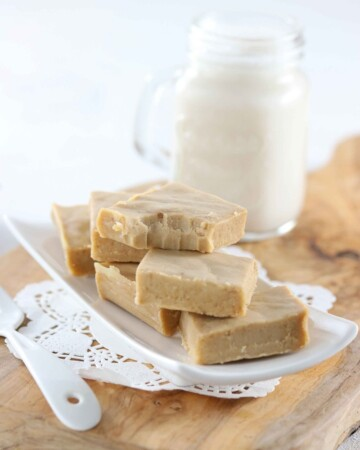 Low Carb Sugar Free Maple Fudge - My PCOS Kitchen - Creamy fudge over a small plate and a glass of almond milk in the background.