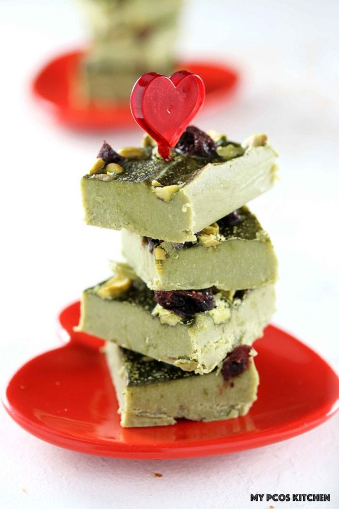 Low Carb Paleo Matcha Chocolate Fudge - My PCOS Kitchen - Green tea fat bombs stacked over one another over a red heart Valentine's Day plate.