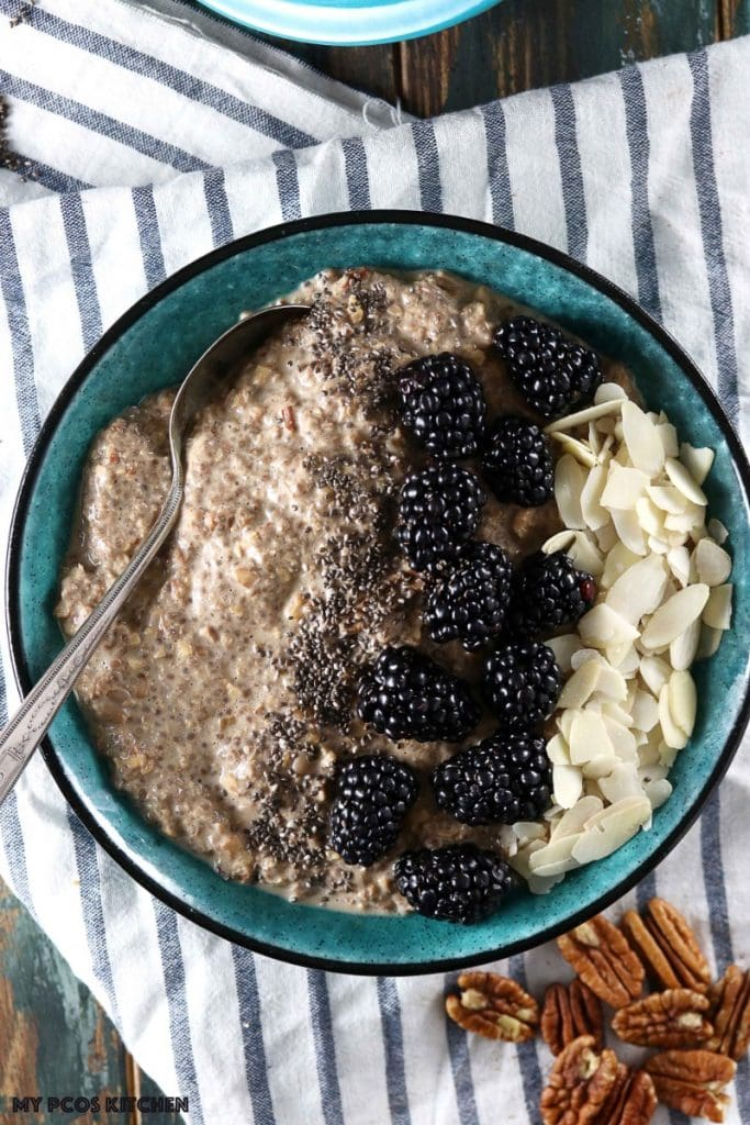 Maple Low Carb Oatmeal - My PCOS Kitchen - An overhead shot of chia seed paleo oatmeal with blackberries and almond slices in a blue bowl over a linen cloth.