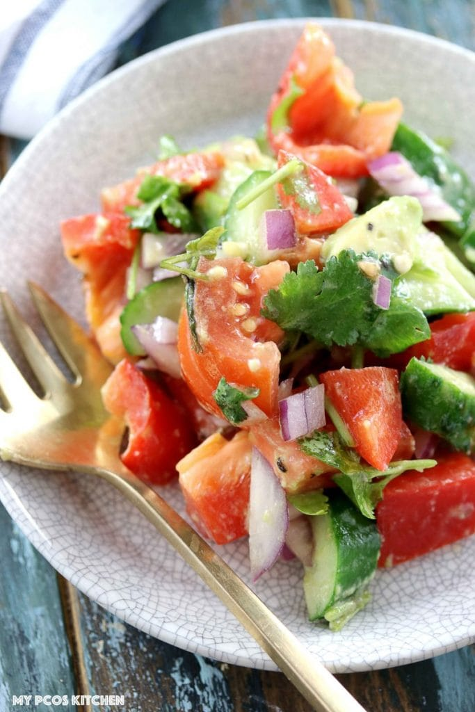 Low Carb Paleo Avocado Cucumber Tomato Salad - My PCOS Kitchen - An overhead shot of this avocado medley salad with tomatoes and fresh cilantro. Brass spoon on the side.