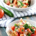 Low Carb Paleo Avocado Cucumber Tomato Salad - My PCOS Kitchen - A small plate of salad in front of a larger plate. A blue wooden background with tomatoes and cucumbers.