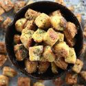 Low Carb Gluten Free Garlic Croutons - My PCOS Kitchen - Gluten free and low carb croutons in a black bowl over a baking tray filled with parsley and parmesan.