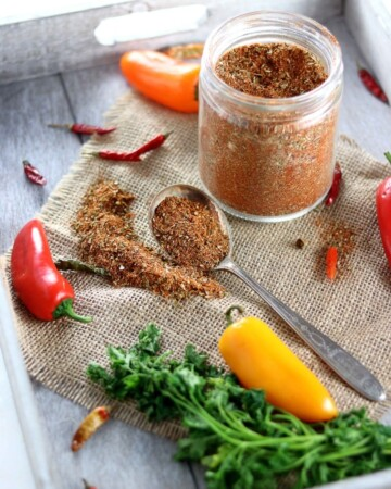 Low Carb Paleo Taco Seasoning - My PCOS Kitchen - A glass jar full of taco spice surrounded by chili peppers and cilantro.