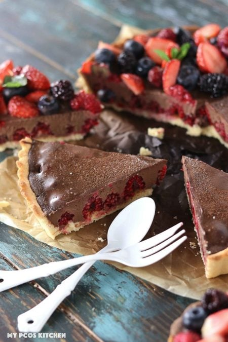 Low Carb No Bake Chocolate Tart with Raspberries - My PCOS Kitchen - White cutlery beside a berry chocolate tart.