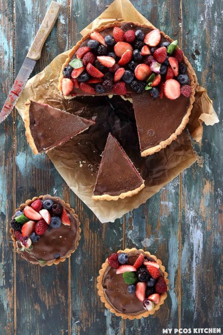 Low Carb No Bake Chocolate Tart with Raspberries - My PCOS Kitchen - Slices cut out of a chocolate raspberry tart.