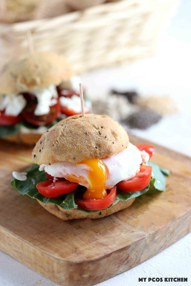 Keto buns used as a sandwich stuffed with a runny egg, tomatoes and spinach.