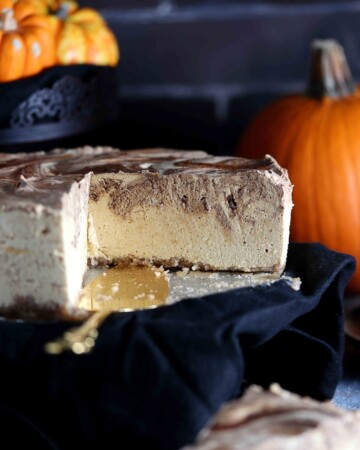 A large pumpkin cheesecake on a cake platter that has two slices missing. Pumpkins in the background.