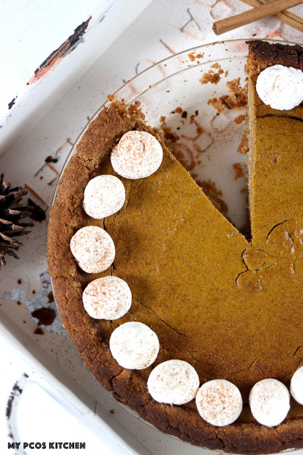 A slice missing out of a round paleo pumpkin pie.
