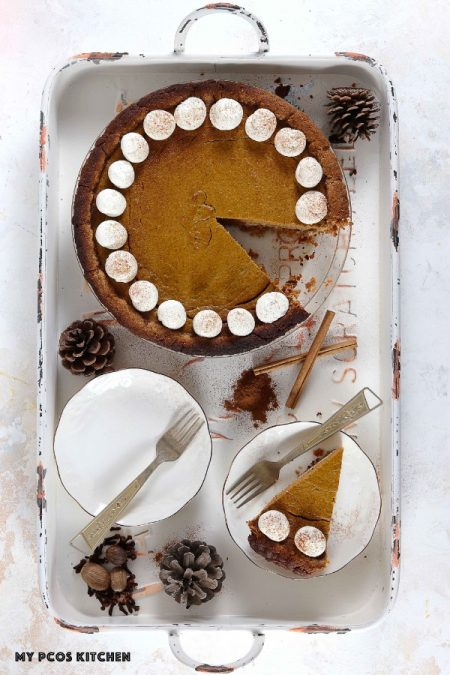 Photo of pumpkin pie with a slice cut on a white plate over a white metal tray.