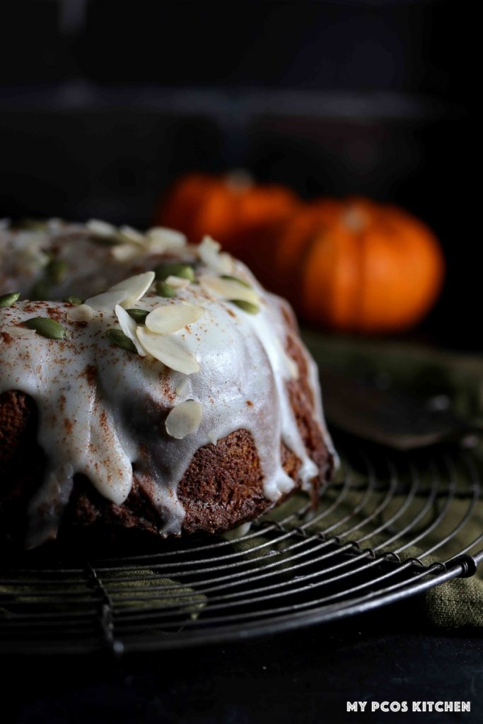 A pumpkin bundt cake resting on a vintage french cooling rack.