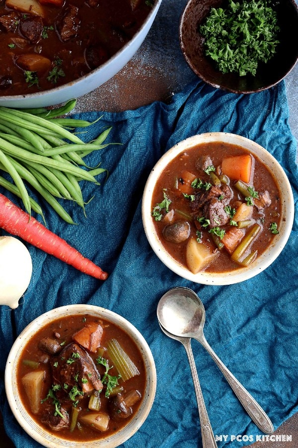 Two bowls of homemade beef stew with a dutch oven filled with more.