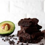 Four sugar free brownies stacked on top of one another with some avocado in the background.