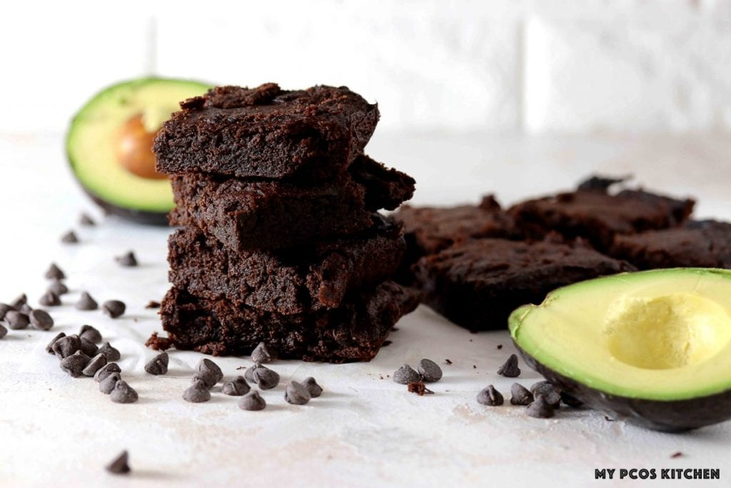 Fudgy chocolate keto brownies made with avocado stacked on top of one another.