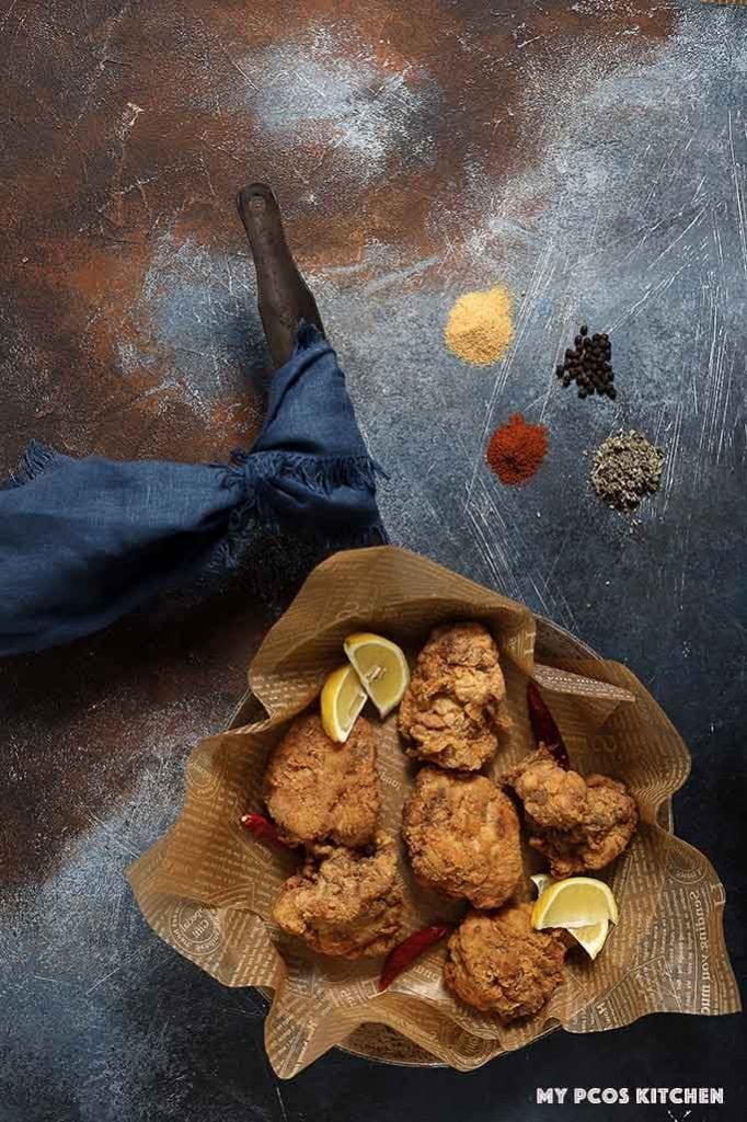 Crispy fried chicken thighs over parchment paper in an old rustic frying pan.