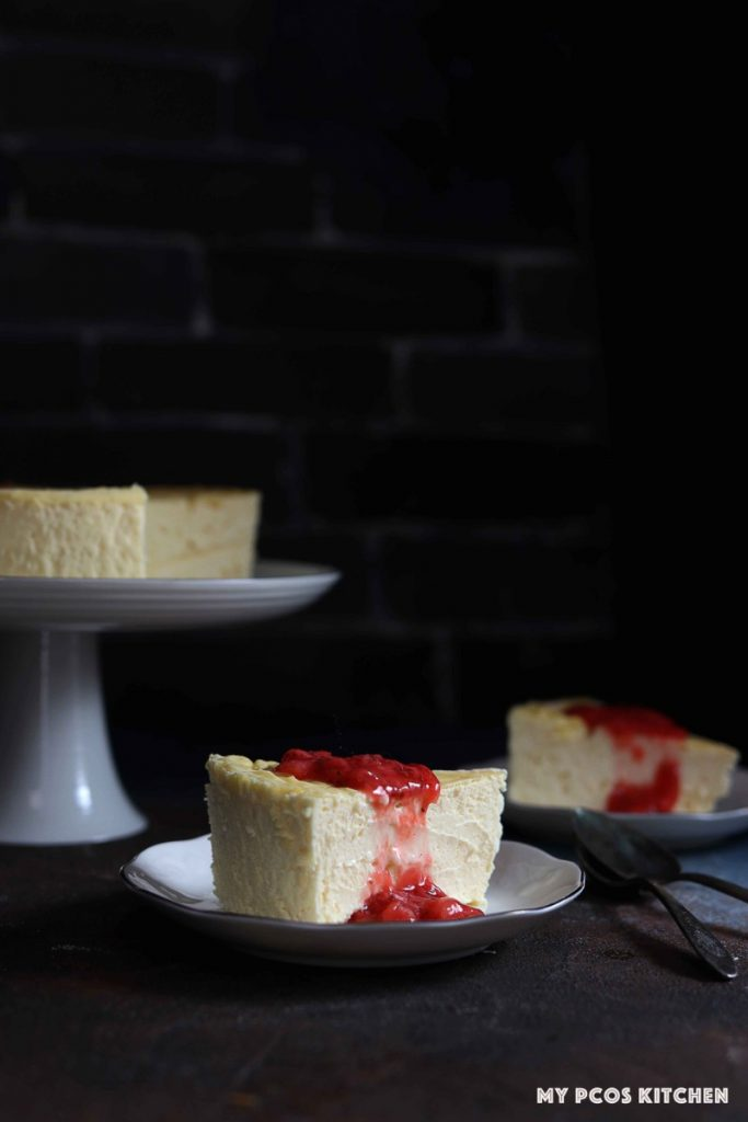 Two slices of sugar free cheesecake with a low carb strawberry sauce poured over on two small plates with a whole cheesecake in the background on a white cake stand.