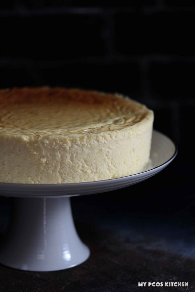 A crack free keto cheesecake on a white cake stand.